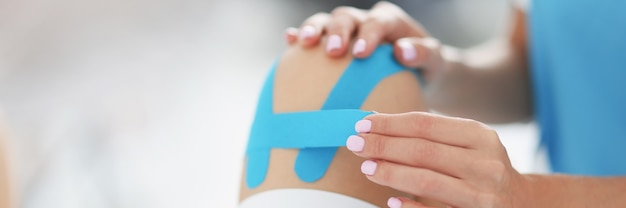 Doctor fixes kinesio tape on patients leg