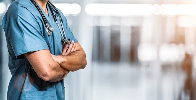 Doctor in front of a blue blurred hospital background