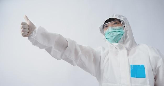 의사 제스처 ppe 정장 또는 개인 보호 장비 몸짓과 지적에 아시아 여자 의사. 흰색 의료 고무 장갑. 고글 안경과 녹색 n95 마스크는 유행성 코로나 바이러스를 보호합니다.
