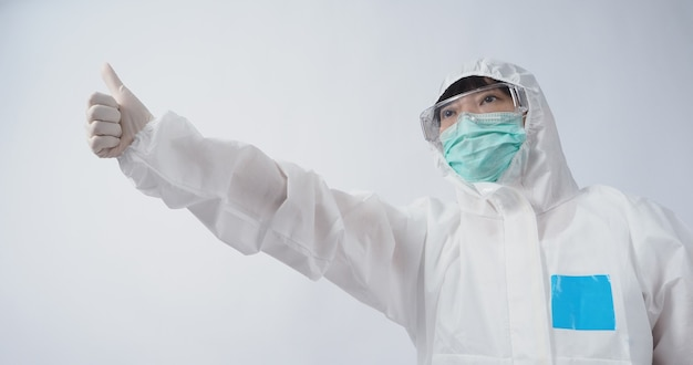 Doctor gesture asian woman doctor in ppe suit or personal protection equipment gesturing and point out. white medical rubber gloves. goggles glasses and green n95 mask to protect pandemic coronavirus.