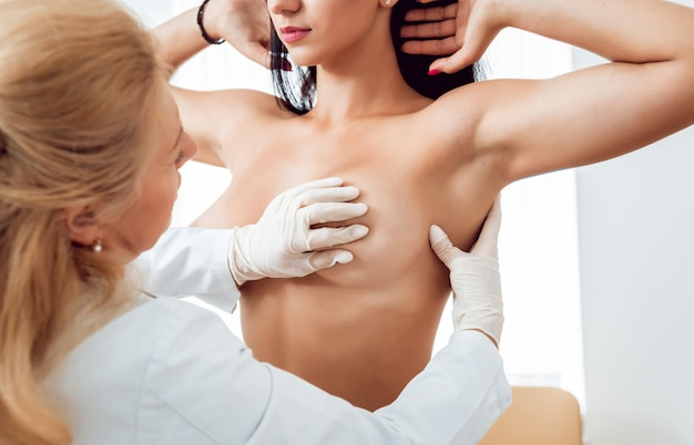 Doctor get examining breast of young woman.