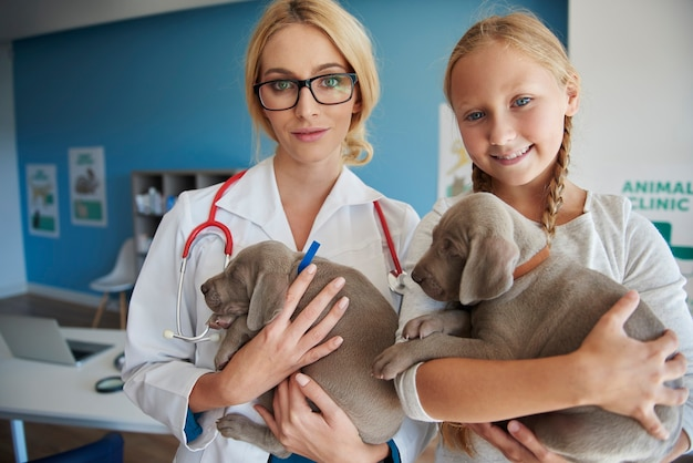 Medico e ragazza che tengono simpatici cuccioli Foto Gratuite