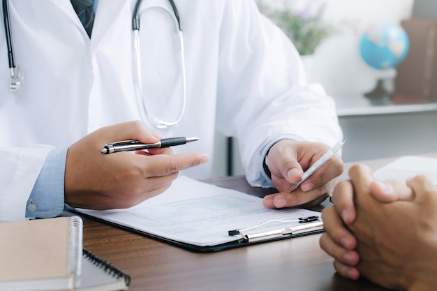 Doctor give recommend pills or drugs to unhealthy mature male patient in clinic