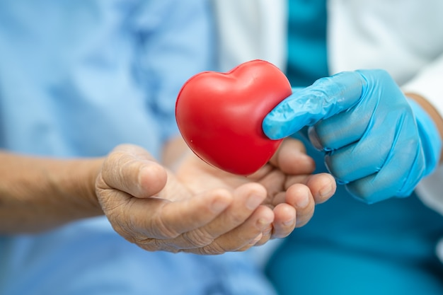 Doctor give red heart to asian senior woman patient