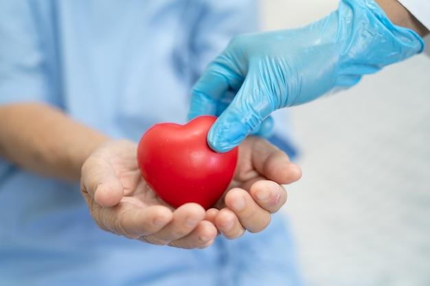 医者はアジアのシニアまたは高齢の老婦人女性患者に赤い心を与える