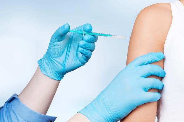 Врач дает пациенту в клинике шприц с вакциной.