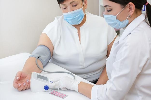 Врач дает пациенту таблетки от давления. врач измеряет артериальное давление у взрослого человека