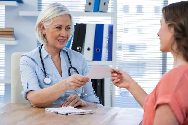 의료 사무실에서 그녀의 환자에게 처방전을주는 의사