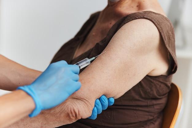 팔 예방 접종 코로나바이러스에 주사를 맞는 의사
