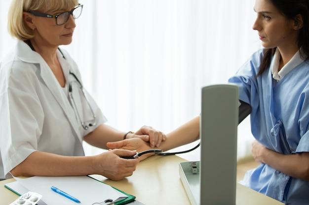 조언을 하는 의사와 테이블에 앉아 있는 동안 뭔가에 대해 토론하는 환자 미소
