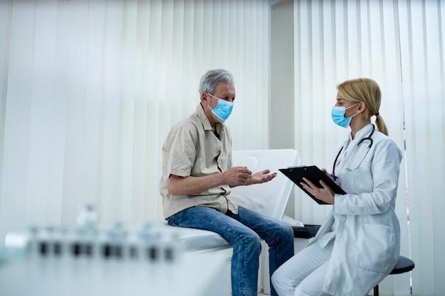 コロナウイルスのパンデミック時に健康を維持するためのアドバイスを老人に与える医師。