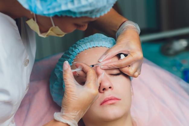 눈썹 사이의 이마에 중간 나이 여자에 얼굴 리프팅 주사를주는 의사가 주름을 제거합니다