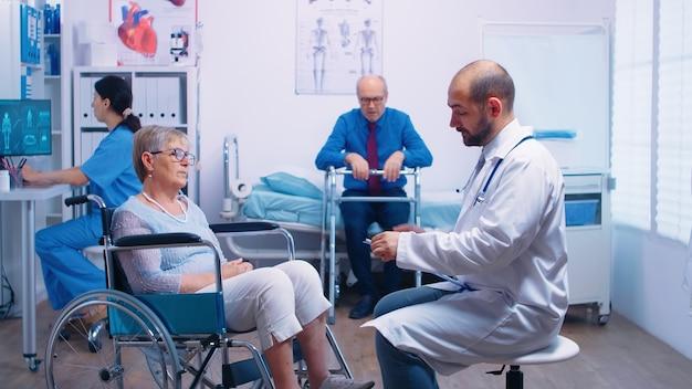 휠체어를 탄 노인 은퇴한 장애인 여성을 위해 회복 클리닉에서 의료 상담을 하는 의사. 의료 의료 지원 및 노인 간호 지원을 위한 지원 치료