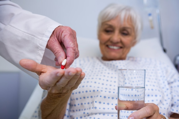 Doctor giving medicine pill to senior patient