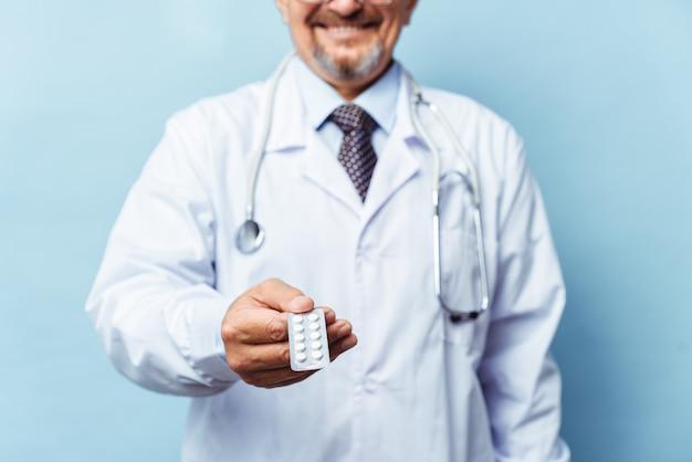 Доктор, давая таблетки. на синем фоне. понятие медицины, фармакологии, здравоохранения.
