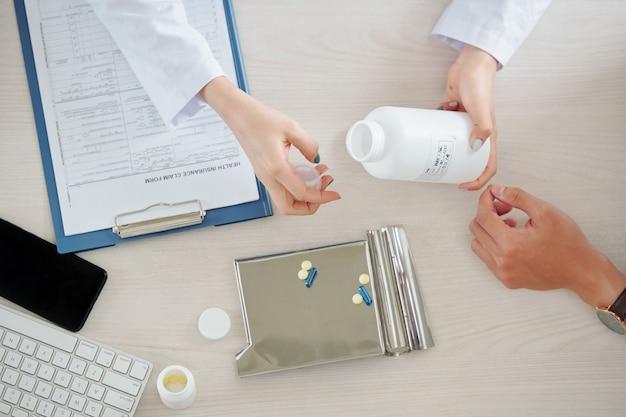 医者は患者の錠剤や錠剤を与える
