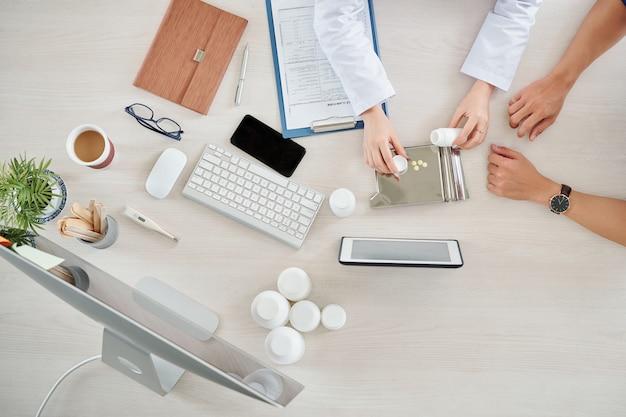 医者は患者に薬を与える