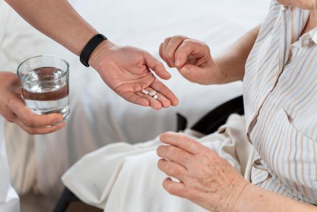 Doctor giving pills to her patient