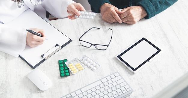 Доктор дает таблетки пожилой женщине. здоровье, медицина, уход