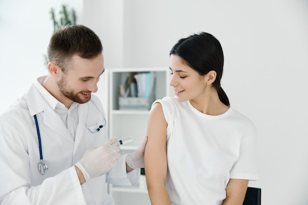 Doctor giving a shot to a woman in the shoulder vaccination epidemic hospital