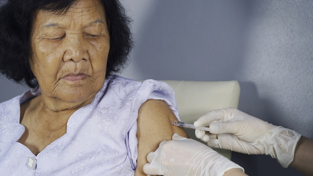 Doctor giving vaccine injection into senior woman