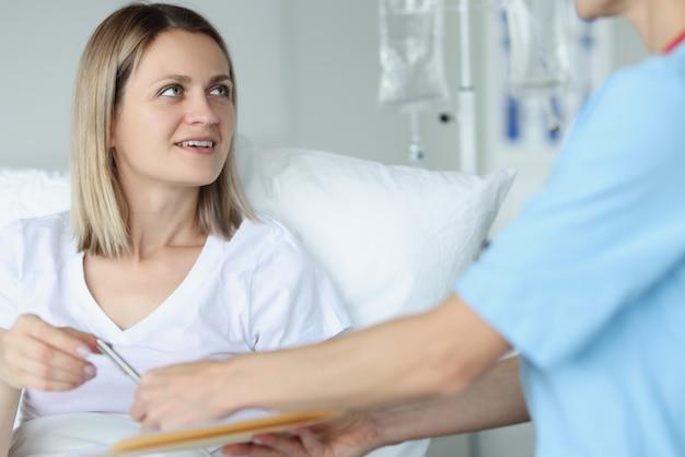 クリニックで女性患者にボールペンを与える医師。医療介入の概念への同意