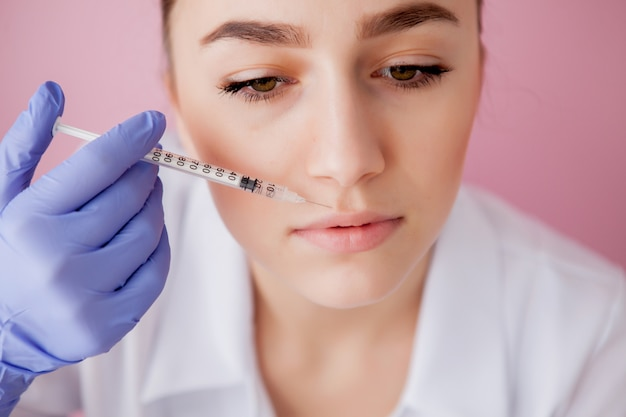 Doctor in gloves giving woman botox injections in lips, on pink wall