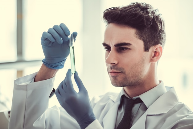 Doctor in gloves is working with test tubes at the lab.