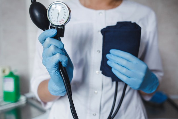 Doctor in gloves with a blood pressure