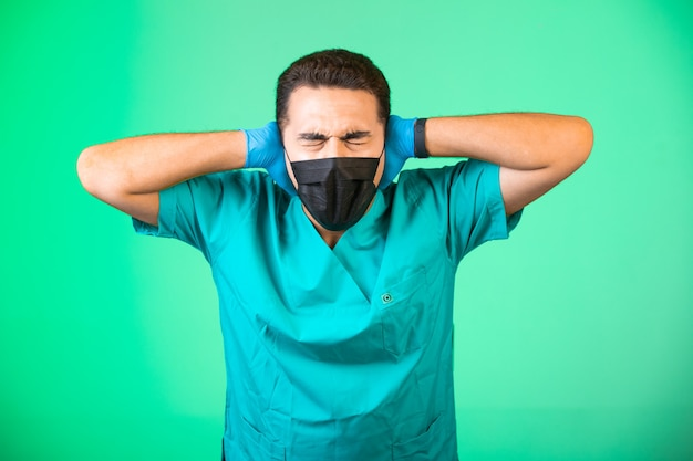Doctor in green uniform and face mask covering his ears.