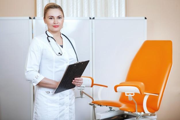 Врач-гинеколог делает записи на планшете в офисе возле оранжевого стула