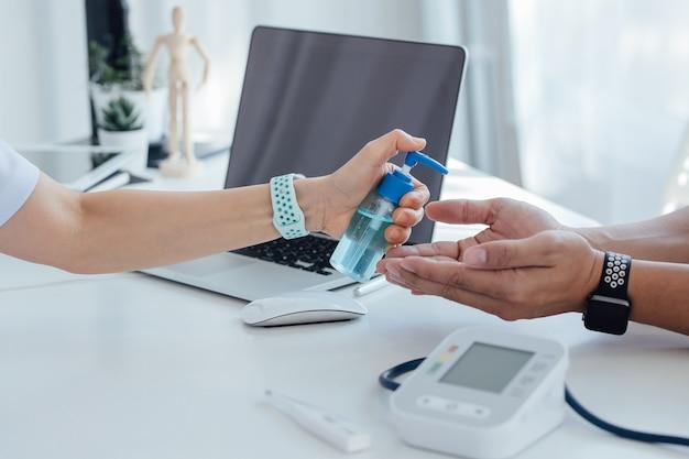 医師の手持ちのアルコールボトル、感染性ウイルスに対する保護のために男性の手にゲル