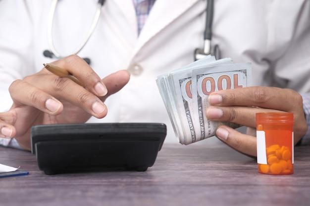 의사가 손을 현금을 들고 계산기를 사용하여