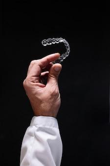 Doctor hand holding a clear dental aligner