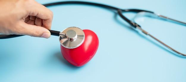 青い背景に赤いハートの形で聴診器を保持している医師の手。ヘルスケア、生命保険、世界心臓デーのコンセプト