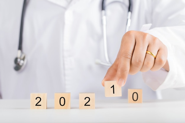2021年の木製ブロックを持っている医者の手。新年と健康の概念。