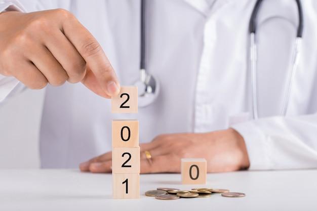 2021 년 나무 블록을 들고 의사 손. 새 해와 건강 개념입니다.