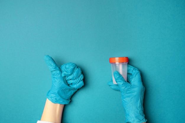 Доктор рука держит пластиковый контейнер для анализа