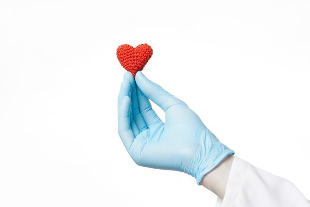 白い背景の上のかぎ針編みの赤いハートを保持している青い手袋の医者の手カーディオケアと愛