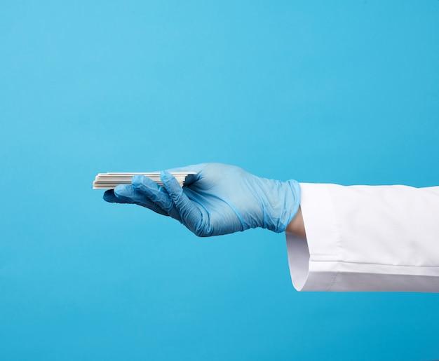Рука доктора в синих медицинских латексных перчатках держит пустую бумажную визитку на синей поверхности