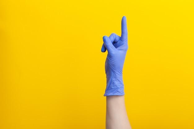 Рука доктора в медицинской сиреневой перчатке для одноразового использования направлена вверх пальцем