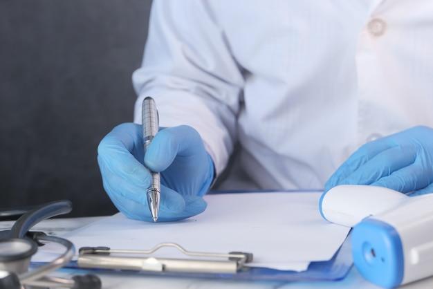 医師は机の上の処方箋を書く保護ガラスに手します。