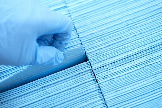 Доктор рука в резиновых перчатках вытаскивает стерильную одноразовую салфетку из упаковки крупным планом