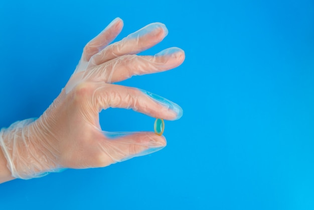 Doctor hand in medical glove holds yellow   fish oil capsule. vitamin d deficite prevention with copy space
