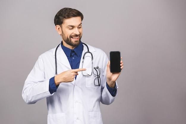 灰色の背景に分離された空白のスマートフォン画面アプリケーションを示す医師の手