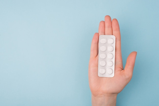 Doctor hand stretching hand to patient and give pills concept. top above overhead first person pov close up view photo of one hand of young female holding blister with pills isolated background