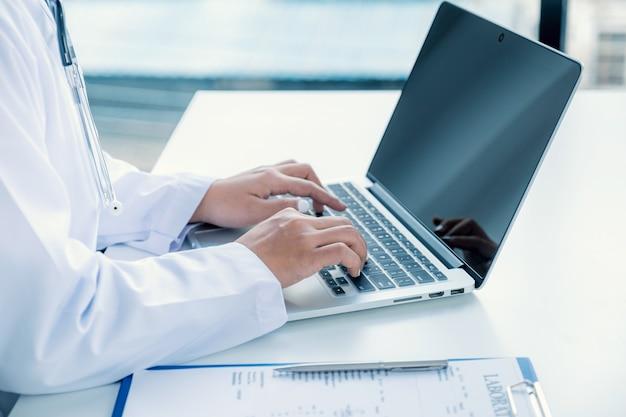 의사가 노트북에 문자 메시지를 보내고 환자의 건강 검진 결과 및 약물 사용을 기록합니다.