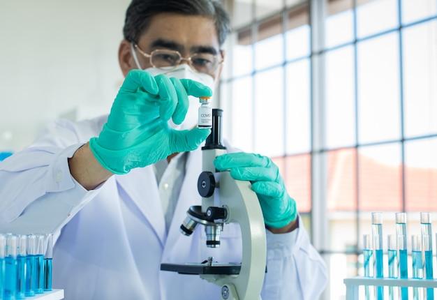 Рука врача в синих одноразовых перчатках, показывающая флакон с вакциной от коронавируса. деталь руки с защитными хирургическими перчатками в лаборатории, держащей во флаконе дозу вакцины, концепцию профилактики и иммунизации