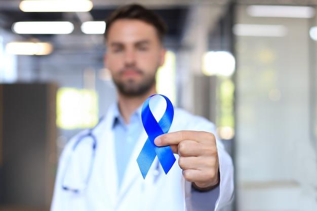 Рука доктора с голубой лентой осведомленности рака простаты. символ неба крупным планом онкологии медицины.