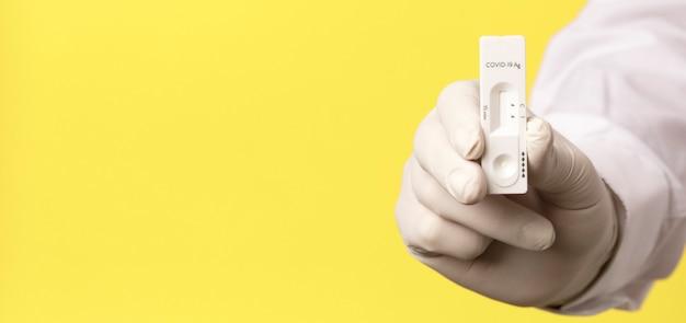 黄色の背景にコロナウイルステストと医師の手